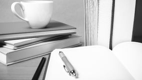 Open notebook with book and coffee cup  black and white color to Royalty Free Stock Images