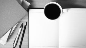 Open notebook with book and coffee cup  black and white color to Stock Photos