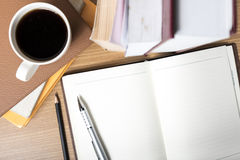 Open notebook with book and coffee cup Royalty Free Stock Photos