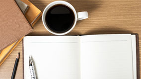 Open notebook with book and coffee cup stock image