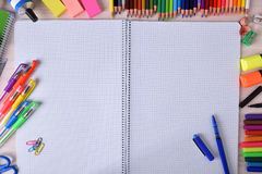 Open notebook in center with school material around Royalty Free Stock Image