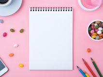 Open notebook with a clean white sheet, caramel, lollipops, mobile phone, crayon, cup of coffee, decorations on a pink bright tab. Open notebook with a clean Stock Photos