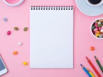 Open notebook with a clean white sheet, caramel, lollipops, mobile phone, crayon, cup of coffee, decorations on a pink bright tab. Open notebook with a clean Royalty Free Stock Photo