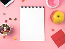 Open notebook with a clean white sheet, caramel, lollipops, telephone, apple, decorations on a pink bright table. Girl`s workplace for creativity, plans and Stock Photo