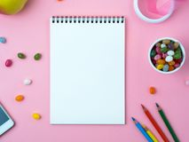 Open notebook with a clean white sheet, sweets, mobile phone, crayon, decorations on a pink bright table. Girl`s workplace for creativity, plans and dreams Stock Image