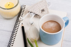 Open notebook, coffe, candle, earpods and tulip Stock Photos