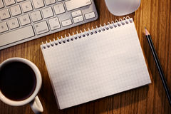 Open notebook with coffee alongside a keyboard. Open notebook with blank white lined pages with a cup of black coffee alongside a computer keyboard on a wooden royalty free stock images