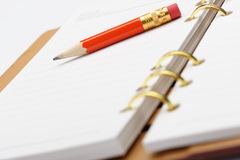 Open notebook with copper binding and red pencil. Photo closeup stock photo