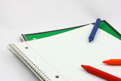 Open Notebook With Crayons. An open spiral notebook with three colorful crayons photographed on a light background Stock Photography