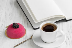 Open notebook and a cup of coffee and cake. Beautiful cake with blackberries, open notebook and cup of coffee horizontally Royalty Free Stock Photo