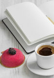 Open notebook and a cup of coffee and cake on the wooden backgro. Beautiful cake with blackberries, open notebook and cup of coffee Stock Photography