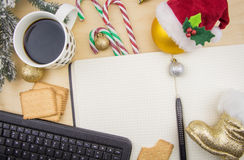Open notebook with cup of coffee, cookies and ornaments. Royalty Free Stock Images