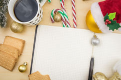 Open notebook with cup of coffee, cookies and ornaments. Royalty Free Stock Photography