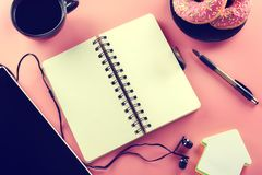Open notebook and cup of coffee with donut on a pink background. Tinted picture. Top view, Open notebook and cup of coffee with donut on a pink background Stock Images