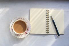 Open notebook and cup of tea on a sunny table top. Open notebook and cup of tea in a vintage cup and saucer on a sunny table top royalty free stock photography