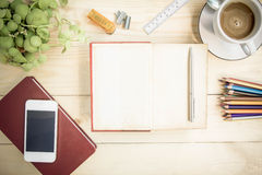 Open notebook diary on wooden table with coffee, Vintage Style. Stock Photo