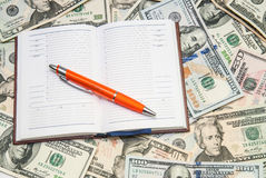 Open notebook with dollars background Royalty Free Stock Image