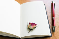 Open Notebook With Dry Rose On Wooden Table With Copy Space Royalty Free Stock Images