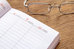 An open notebook and eyeglasses on wood background Royalty Free Stock Photo