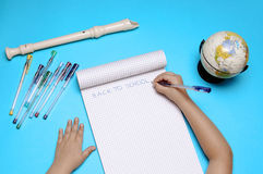 Open notebook with flute, globe and hands of Caucasian girl. Stock Photography