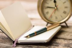 Open notebook with fountain pen and alarm clock Stock Image