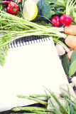 Open notebook and fresh vegetables Royalty Free Stock Photography