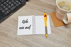 Open notebook with German text `Gib Nie Auf` Never Give Up and a cup of coffee on wooden background. Stock Photos