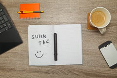 Open notebook with German text `GUTEN TAG` Good afternoon and a cup of coffee on wooden background. Top down view stock photo