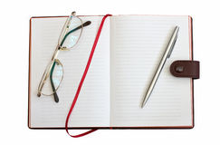 Open notebook with glasses and pen. On white background stock image