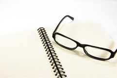 Open notebook with glasses Royalty Free Stock Images