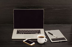 Open notebook, graphics tablet, coffee cup and phone on a black table Stock Photo