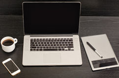 Open notebook, graphics tablet, coffee cup and phone on a black table Royalty Free Stock Photography