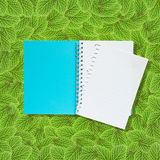 Open notebook on green leafs Stock Image