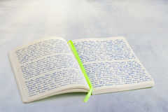 Open notebook with handwritten lorem ipsum text and ribbon book. Mark in the middle, laying on textured surface stock image