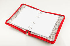 Open notebook, isolated on white background. Open notebook, in red folder with zipper, isolated on white background Stock Images