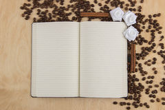 Open notebook with lined pages on a table on which are scattered Stock Photography