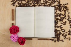Open notebook with lined pages on a table on which are scattered Stock Image