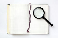 Open notebook with magnifying glass Stock Photos