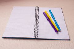 Open notebook with multi-colored markers . On light background.  Royalty Free Stock Image