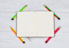 Open notebook with newly sharpen pencils on white desktop. High angled view of open notebook with newly sharpen pencils placed at each corner on top of rustic Stock Photo
