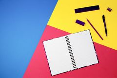 Open notebook and office supplies on colorful background Royalty Free Stock Photos