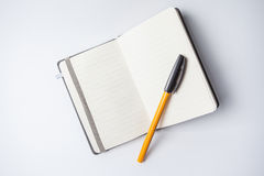 Open notebook with an orange ballpen on it Royalty Free Stock Photography