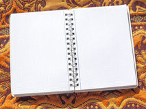 Open notebook on oriental fabric. Background Stock Photo