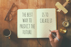 Open notebook over wooden table with motivational saying Stock Photo
