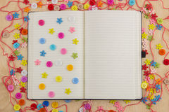 Open notebook page needlewoman with buttons, thread, flowers and. Open notebook page needlewoman with multicolored buttons, thread, flowers and hearts Royalty Free Stock Photo