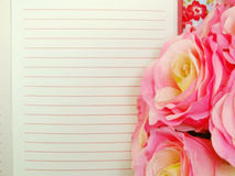 Open notebook paper with red lines and artificial roses flower Royalty Free Stock Image