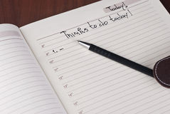 Open notebook and pen. To do list with pen on table Royalty Free Stock Photo