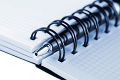Open notebook and pen, with blue tint royalty free stock image
