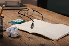 Open notebook with a pen and calculator on wooden table Stock Image
