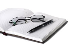 Open notebook with pen and glasses Stock Photos